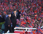 In this Thursday, June 20, 2019, file photo released by China's Xinhua News Agency, spectators wave Chinese and North Korean flags as North Korean leader Kim Jong Un, left, and visiting Chinese President Xi Jinping attend a mass gymnastic performance at the May Day Stadium in Pyongyang, North Korea. North Korean leader Kim Jong Un, meeting in Pyongyang with Chinese President Xi Jinping, said Thursday that his country is waiting for a desired response in stalled nuclear talks with the United States. (Yan Yan/Xinhua via AP, File)