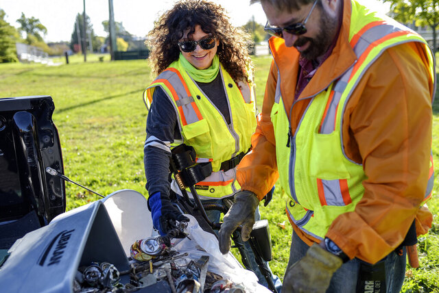 Scott, right, and Debby Bates sift through a bin of dangerous objects they removed from area parks on Wednesday, Oct. 7, 2020, at Marshall Park in Lansing, Mich. (Nick King/Lansing State Journal via AP)