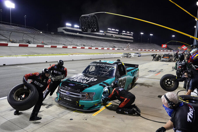 Ben Rhodes makes a pit stop during the NASCAR Truck Series auto race Thursday, Sept. 10, 2020, in Richmond, Va. (AP Photo/Steve Helber)