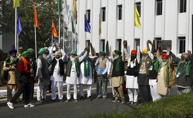 Representatives of various farmers organizations hold hands before the media as they arrive for talks with the government representatives in New Delhi, India, Thursday, Dec.3, 2020. Tens and thousands of farmers have descended upon the borders of New Delhi to protest new farming laws that they say will open them to corporate exploitation. (AP Photo/Manish Swarup)