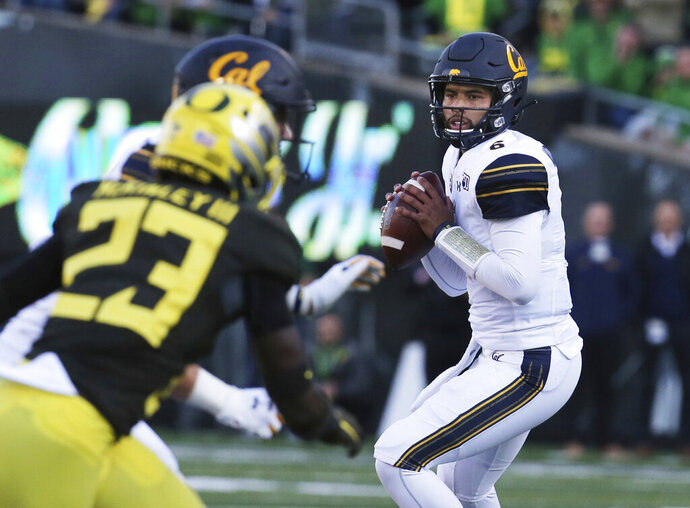 California quarterback Devon Modster, right, looks down field for an open receiver against Oregon during the first quarter of an NCAA college football game Saturday, Oct.. 5, 2019, in Eugene, Ore. (AP Photo/Chris Pietsch)