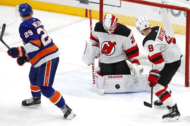 New York Islanders center Brock Nelson (29) looks over his shoulder as New Jersey Devils goaltender Mackenzie Blackwood (29) blocks a shot with Devils defenseman Will Butcher (8) watching during the third period of an NHL hockey game, Thursday, Jan. 2, 2020, in Uniondale, N.Y. (AP Photo/Kathy Willens)