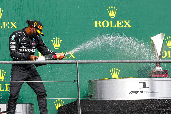 Mercedes driver Lewis Hamilton of Britain steers celebrates on the podium after winning the Formula One Grand Prix at the Spa-Francorchamps racetrack in Spa, Belgium, Sunday, Aug. 30, 2020. (Francois Lenoir/Pool Photo via AP)