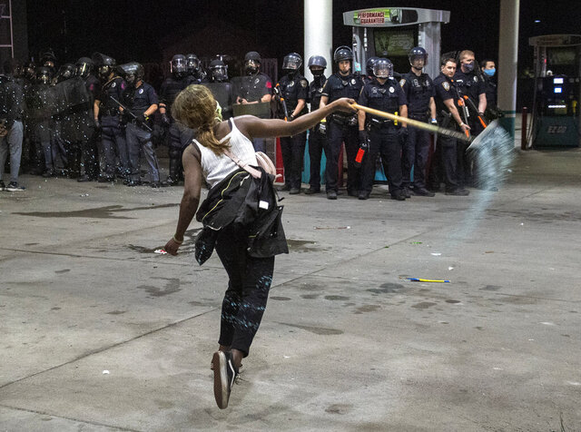 A protester throws a window cleaner at police standing guard of an Ez Go gas station after the station was damaged following a protest of the killing of George Floyd, early Saturday, May 30, 2020 in Lincoln, Neb.  Floyd died after being restrained by Minneapolis police officers on Memorial Day.  (Justin Wan/Lincoln Journal Star via AP)