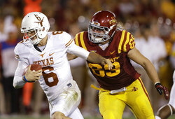 FILE - In this Oct. 3, 2013, file photo, Texas quarterback Case McCoy runs from Iowa State's Nick Kron during the second half of an NCAA college football game in Ames, Iowa. Kron was arrested in connection with an assault of a University of Iowa basketball star in May. Kron, 29, of Nashville, Tenn., faces an assault causing bodily injury charge for allegedly attacking Jordan Bohannon, a Hawkeye guard, outside a downtown Iowa City, Iowa, bar. (AP Photo/Charlie Neibergall, File)