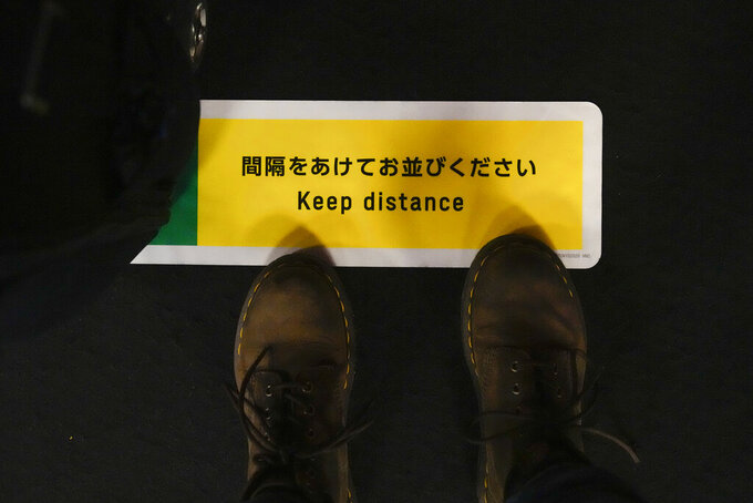 Associated Press photographer stands on a social distance marker while waiting to get her 2020 Summer Olympics credential validated before leaving Haneda Airport in Tokyo, Monday, July 19, 2021. (AP Photo/Natacha Pisarenko)