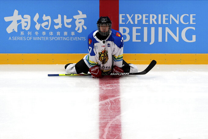 A Capital Institute hockey team player stretches during a practice session at the ice hockey venue set for the 2022 Beijing Winter Olympics during a test event at the National Indoor Stadium in Beijing, Thursday, April 1, 2021. Chinese capital holds 10 days test events for 2022 Beijing Winter Olympics in five different venues from April 1-10 and becomes the first city to hold both the Winter and Summer Olympics. (AP Photo/Andy Wong)