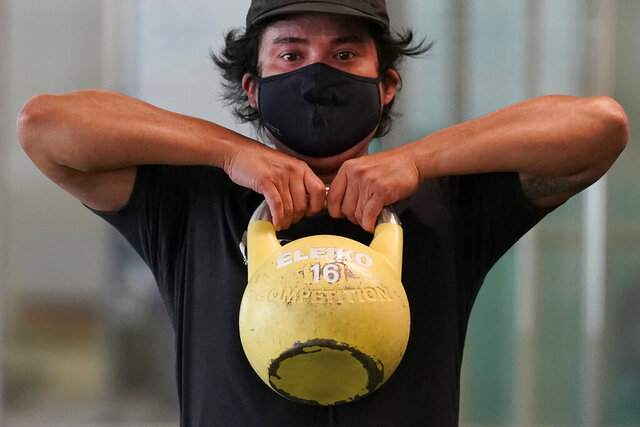Tim Robles wears a mask while lifting a kettlebell during a workout at Fitness SF Transbay gym during the coronavirus outbreak in San Francisco, Tuesday, Sept. 15, 2020. (AP Photo/Jeff Chiu)