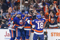 Fans watch New York Islanders' Brock Nelson, second from right celebrates with teammates after scoring a goal during the second period of Game 6 during an NHL hockey second-round playoff series against the Boston Bruins Wednesday, June 9, 2021, in Uniondale, N.Y. (AP Photo/Frank Franklin II)