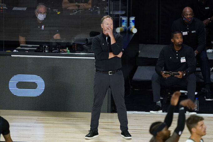 Milwaukee Bucks head coach Mike Budenholzer watches from the bench during the first half of an NBA basketball first round playoff game against the Orlando Magic Monday, Aug. 24, 2020, in Lake Buena Vista, Fla. (AP Photo/Ashley Landis, Pool)