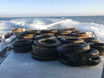 FILE - This Oct. 12, 2017, file photo provided by the California Coastal Commission/UC Davis shows a pile of scrap tires after they were pulled out of the water off Balboa Peninsula in Newport Beach, Calif. California may ask tire manufacturers to look at ways of eliminating zinc from their products because studies have shown the mineral may harm aquatic wildlife when it is washed into rivers and lakes. (California Coastal Commission/UC Davis via AP, File)