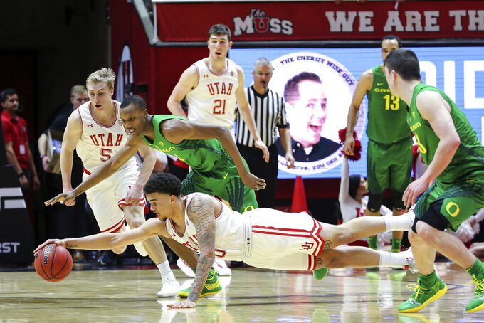 Utah forward Timmy Allen (20) dives in front of Oregon forward Louis King (2) to grab the ball during the second half of an NCAA college basketball game Thursday, Jan. 31, 2019, in Salt Lake City. Oregon won 78-72. (AP Photo/Chris Nicoll)