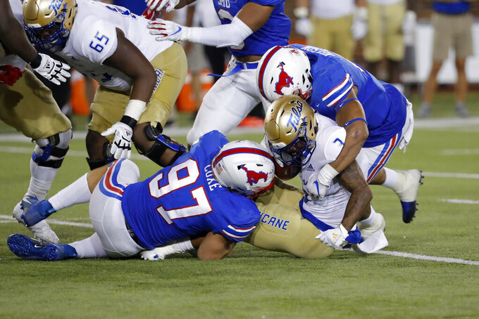 Tulsa running back Shamari Brooks (3) is tackled by SMU defensive end Turner Coxe (97) and linebacker Patrick Nelson, top right, during the first half of an NCAA college football game, Saturday, Oct. 5, 2019, in Dallas, Texas. (AP Photo/Roger Steinman)