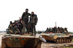 In this photo released Wednesday, Feb. 12, 2020, by the Syrian official news agency SANA, Syrian government soldiers on their armored vehicles patrol the highway that links the capital Damascus with the northern city of Aleppo, Syria. The M5 highway, recaptured by President Bashar Assad's forces this week, is arguably the most coveted prize in Syria's civil war. The strategic highway is vital for Syria's  economy as well as for moving troops. (SANA via AP)