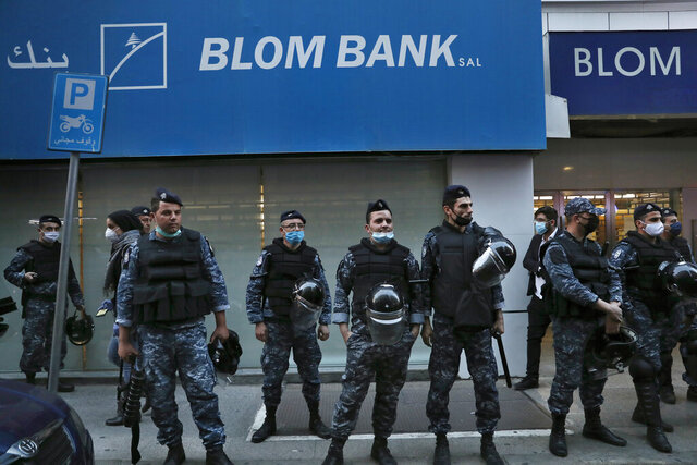 Lebanese riot police stand guard in front of a bank entrance, after the anti-government protesters try to destroy banks windows during a protest against the Lebanese central bank's governor Riad Salameh and against the deepening financial crisis, at Hamra trade street, in Beirut, Lebanon, Thursday, April 23, 2020.   (AP Photo/Hussein Malla)