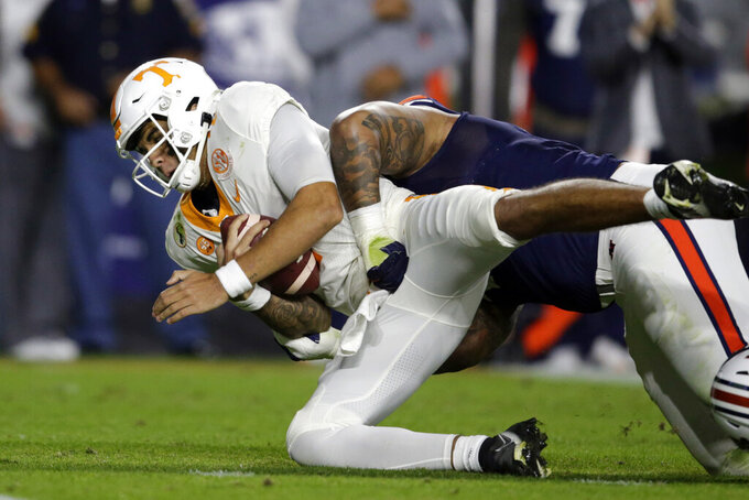 Tennessee quarterback Jarrett Guarantano, left, is sacked by Auburn defensive tackle DaQuan Newkirk during the first half of an NCAA college football game Saturday, Nov. 21, 2020, in Auburn, Ala. (AP Photo/Butch Dill)