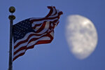 FILE - In this June 29, 2020, file photo, a flag flies in the wind above City Hall as the waxing gibbous moon passes behind clouds overhead in Kansas City, Mo. (AP Photo/Charlie Riedel, File)