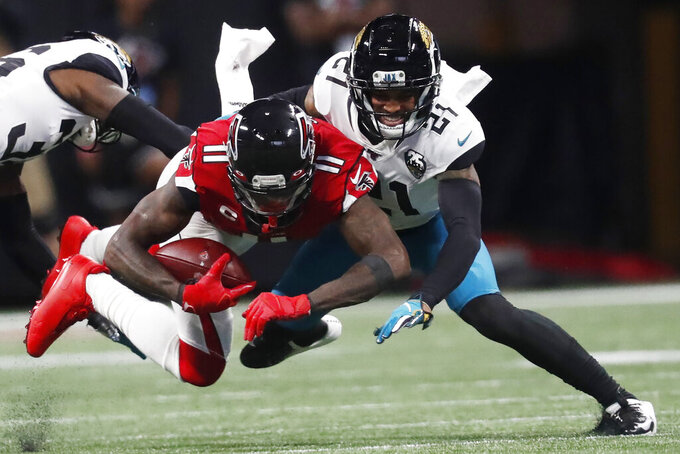 Jacksonville Jaguars cornerback A.J. Bouye (21) tackles Atlanta Falcons wide receiver Julio Jones (11) during the first half of an NFL football game, Sunday, Dec. 22, 2019, in Atlanta. (AP Photo/John Bazemore)