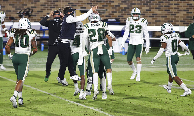 Charlotte coach Will Healy celebrates a turnover with his players during the first half against Duke in an NCAA college football game Saturday, Oct. 31, 2020, in Durham, N.C. (Jaylynn Nash/Pool Photo via AP)