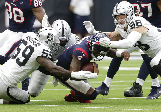 Houston Texans quarterback Deshaun Watson (4) is hit by Oakland Raiders defenders Tahir Whitehead (59) and Maxx Crosby (98) during the first half of an NFL football game Sunday, Oct. 27, 2019, in Houston. (AP Photo/Michael Wyke)
