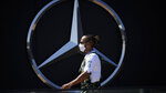 Mercedes driver Lewis Hamilton of Britain walks past a Mercedes logo in the paddock ahead of the Spanish Formula One Grand Prix at the Barcelona Catalunya racetrack in Montmelo, just outside Barcelona, Spain, Thursday, May 6, 2021. The Spanish Grand Prix will be held on Sunday. (AP Photo/Emilio Morenatti)