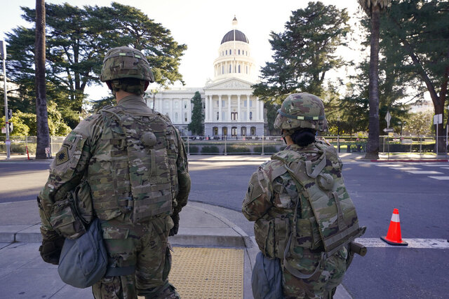 Members of the California National Guard walk past the California state Capitol in Sacramento, Calif., Wednesday, Jan. 20, 2021. A temporary 6-foot high chain link fence surrounds the Capitol and California Gov. Gavin Newsom mobilized the National guard last week over concerns that protests around the inauguration of President Joe Biden could turn violent and destructive. (AP Photo/Rich Pedroncelli)