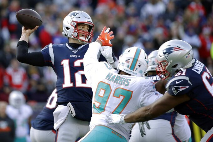 New England Patriots quarterback Tom Brady, left, passes under pressure from Miami Dolphins defensive end Trent Harris in the first half of an NFL football game, Sunday, Dec. 29, 2019, in Foxborough, Mass. (AP Photo/Elise Amendola)