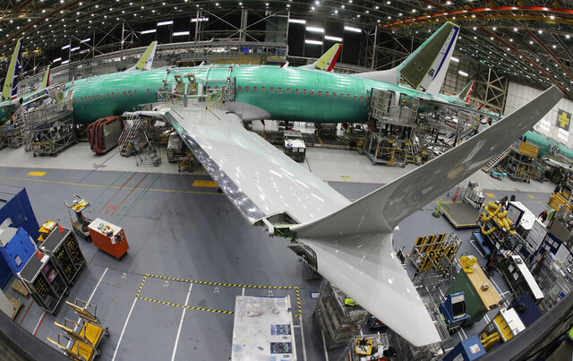 FILE - In this March 27, 2019, photo taken with a fish-eye lens, a Boeing 737 MAX 8 airplane sits on the assembly line during a brief media tour in Boeing's 737 assembly facility in Renton, Wash. The looming production shutdown of Boeing 737 Max jets is taking a toll on a key supplier. Spirit AeroSystems Holdings Inc. is asking employees if they will take voluntarily buyouts. Spirit suspended production of fuselages and other parts for the Max on Jan. 1, 2020, after Boeing told the Wichita, Kansas, company to suspend shipments. (AP Photo/Ted S. Warren)