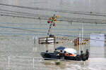 Japan Ground Self-Defense Force members evacuate people to a safer place by boat in Kuma village, Kumamoto prefecture, southwestern Japan, Sunday, July 5, 2020. Heavy rain in the Kumamoto region triggered flooding and mudslides Saturday and left dozens still being stranded at their homes and other facilities. (Kota Endo/Kyodo News via AP)