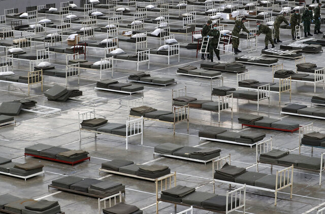 In this March 24, 2020, photo, Serbian soldiers set up beds for treatment of possible COVID-19 infected patients inside of the Belgrade Fair, Serbia. In the ex-communist Europe and elsewhere, rulers are assuming more power while they introduce harsh measures they say are necessary to halt coronavirus spread.  (AP Photo/Darko Vojinovic)