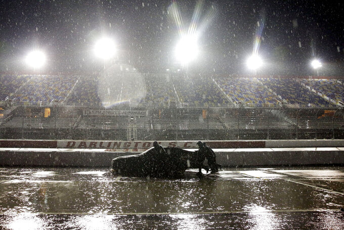 A crew pushes a car through the pit area at Darlington Raceway after the NASCAR Xfinity series auto race was postponed because of rain on May 19, 2020, in Darlington, S.C. (AP Photo/Brynn Anderson)