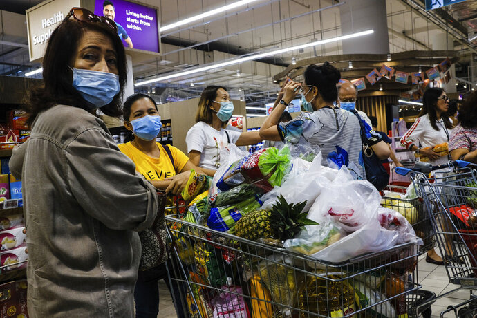 Shoppers wearing face masks with a cart full of food supplies wait in line to pay at a supermarket counter in Singapore, Tuesday, Mar. 17, 2020. Singaporeans were seen buying food supplies in supermarkets following neighboring Malaysia's announcement of a nationwide lockdown from the coronavirus to begin Wednesday which could affect the flow of food supplies to the city state. (AP Photo/Ee Ming Toh)