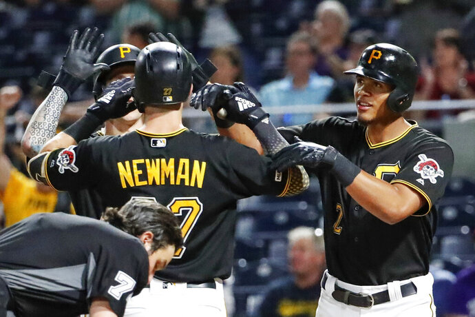 Pittsburgh Pirates' Kevin Newman center, is greeted by Steven Brault, left, and Erik Gonzalez after driving them in with a three-run home run against the Cincinnati Reds in the fifth inning of a baseball game, Friday, Sept. 27, 2019, in Pittsburgh. (AP Photo/Keith Srakocic)