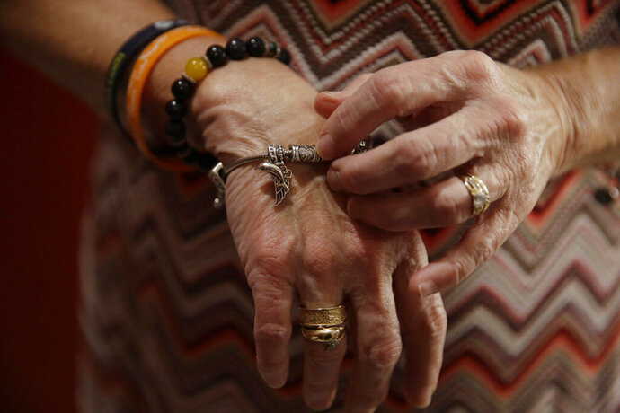Debbi Hixon, fiddles with a finger print charm, on a bracelet that her husband Chris Hixon gave her before he died on Friday, Feb. 14, 2020, in Hollywood, Fla. Hixon was killed in a school shooting on Valentine's Day two years ago at Marjory Stoneman Douglas High School. His widow Debbi recently had the family home renovated by the program