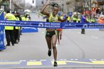 FILE - In this April 20, 2015, file photo, Caroline Rotich, of Kenya, crosses the finish line to win the women's division of the Boston Marathon in Boston. Due to the COVID-19 virus pandemic, the 124th running of the Boston Marathon was postponed from its traditional third Monday in April to Monday, Sept. 14, 2020. (AP Photo/Elise Amendola, File)