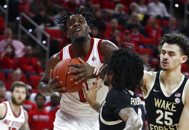 North Carolina State's D.J. Funderburk (0) keeps the ball from Wake Forest's Sharone Wright Jr. (2) and Ismael Massoud (25) during the first half of an NCAA college basketball game in Raleigh, N.C., Friday, March 6, 2020. (Ethan Hyman/The News & Observer via AP)