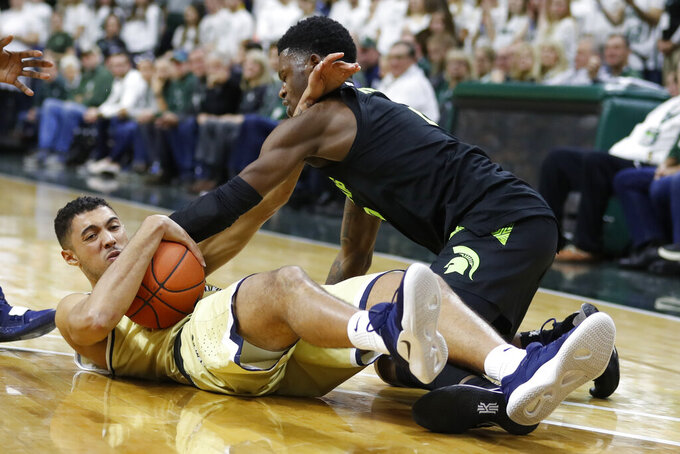 Michigan State guard Rocket Watts, right, is fouled by Charleston Southern forward Duncan LeXander (14) during the second half of an NCAA college basketball game, Monday, Nov. 18, 2019, in East Lansing, Mich. (AP Photo/Carlos Osorio)
