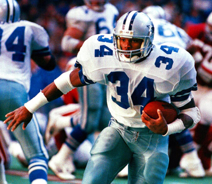 FILE - In this Dec. 27, 1987 file photo Dallas Cowboys running back Herschel Walker carries the ball against the St. Louis Cardinals in Irving, Texas. From the crude, oblong leather helmets to the sparsely padded brown and blue vertical-striped uniforms of the Chicago Bears, it's easy to see how equipment has drastically evolved in the NFL since the days of The Galloping Ghost in the 1920s and '30s. From their heads to their toes, the players' looks through the decades have changed so much, it's tough to believe it's all the same sport.  (AP Photo/Steve Krauss, file)