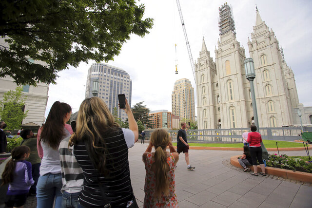 Onlookers gather to watch as the Angel Moroni statue is lowered to the ground by workers from Jacobsen Construction as they remove it from the Salt Lake Temple of The Church of Jesus Christ of Latter-day Saints in Salt Lake City on Monday, May 18, 2020. Removal of the Angel Moroni statue with a crane began Monday as part of a four-year project to renovate and restore the temple. (Scott G Winterton/The Deseret News via AP)
