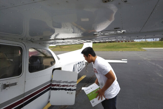 In this March 27, 2020 photo provided by Thomas Kim, TJ Kim, 16, loads medical supplies into a plane in Leesburg, Va., before flying to a hospital in Luray. Kim began delivering donated medical supplies to rural hospitals in need after realizing his flight training could be put to good use during the coronavirus pandemic. (Thomas Kim via AP)