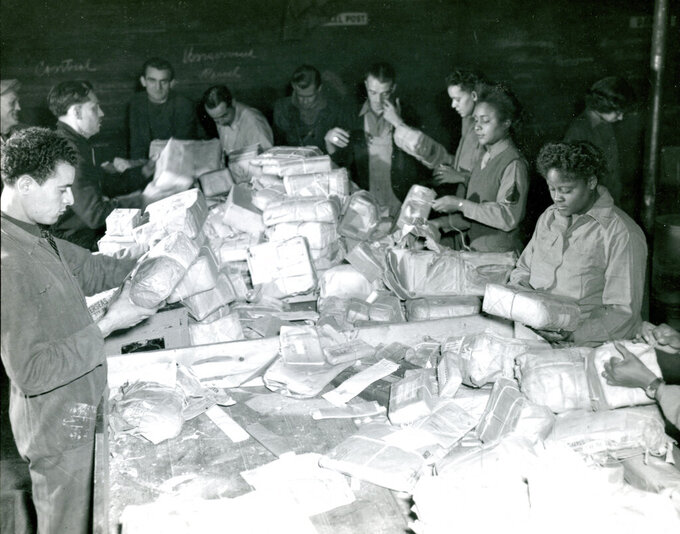 In this photo provided by the U.S. Army Women's Museum, members of the 6888th battalion sort mail with French civilians in Rouen, France, in 1945. The Women's Army Corps battalion, which made history as the only all-female Black unit to serve in Europe during World War II, is set to be honored by Congress. (U.S. Army Women's Museum via AP)