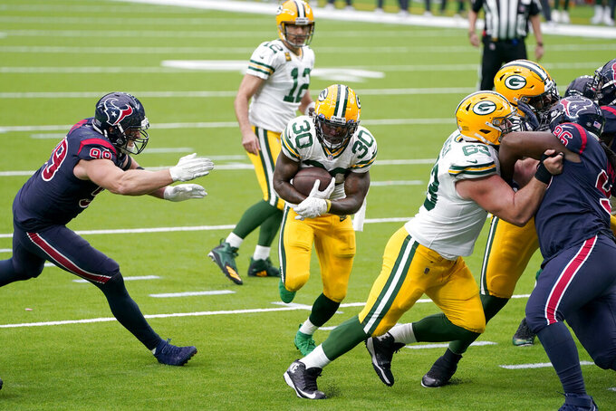 Green Bay Packers running back Jamaal Williams (30) scores past Houston Texans defensive end J.J. Watt, left, during the second half of an NFL football game Sunday, Oct. 25, 2020, in Houston. (AP Photo/Sam Craft)