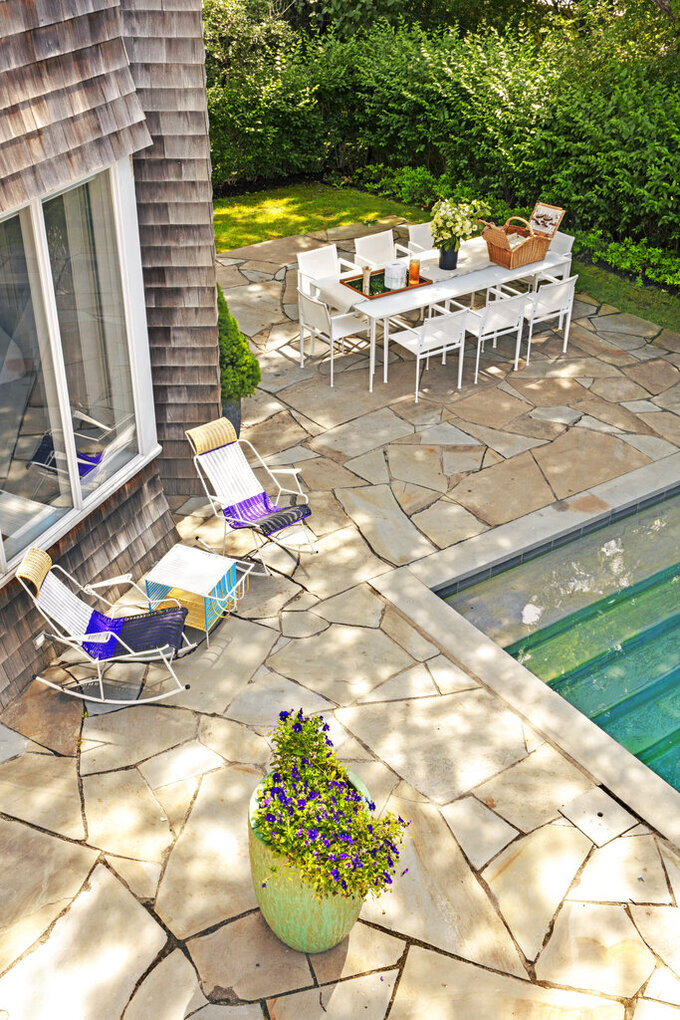 This photo provided by Rottet Studio shows a backyard designed by architect and interior designer Lauren Rottet in Montauk, N.Y. To add color and a lovely scent, Rottet recommends adding a large planter filled with flowering plants, as she did here in this backyard. (Eric Laignel/Rottet Studio via AP)