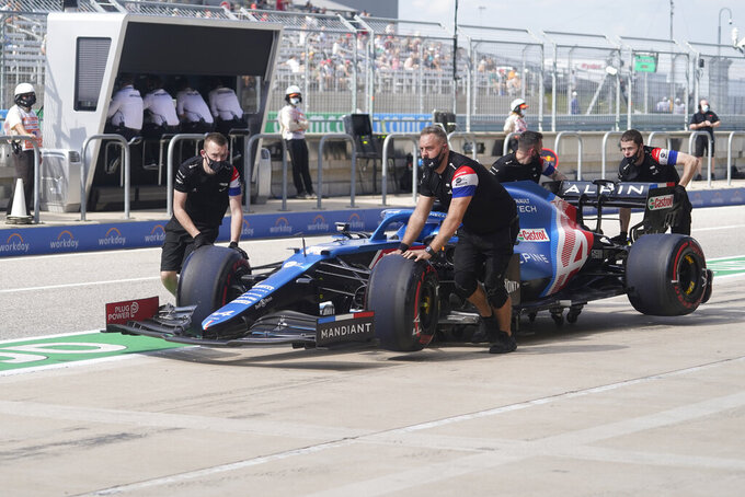 The crew for Alpine driver Fernando Alonso, of Spain, push his car back to the garage during a practice session for the F1 US Grand Prix auto race at the Circuit of the Americas, Friday, Oct. 22, 2021, in Austin, Texas. (AP Photo/Darron Cummings)