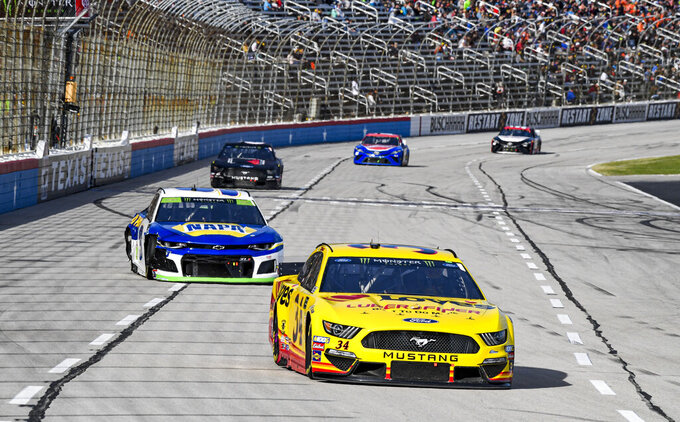 Michael McDowell (34) races into turn one during a NASCAR auto race at Texas Motor Speedway, Sunday, Nov. 3, 2019, in Fort Worth, Texas. (AP Photo/Larry Papke)