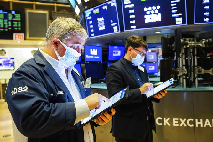 In this photo provided by the New York Stock Exchange, a pair of traders work on the floor, Tuesday Feb. 2, 2021. Stocks were broadly higher in afternoon trading Tuesday, but shares of closely watched companies like GameStop and AMC Entertainment were falling sharply. (Colin Ziemer/New York Stock Exchange via AP)
