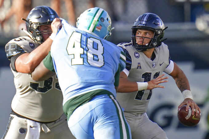 Central Florida quarterback Dillon Gabriel, right, looks for a receiver as offensive lineman Matthew Lee, left, blocks Tulane nose tackle De'Andre Williams (48) during the second half of an NCAA college football game Saturday, Oct. 24, 2020, in Orlando, Fla. (AP Photo/John Raoux)