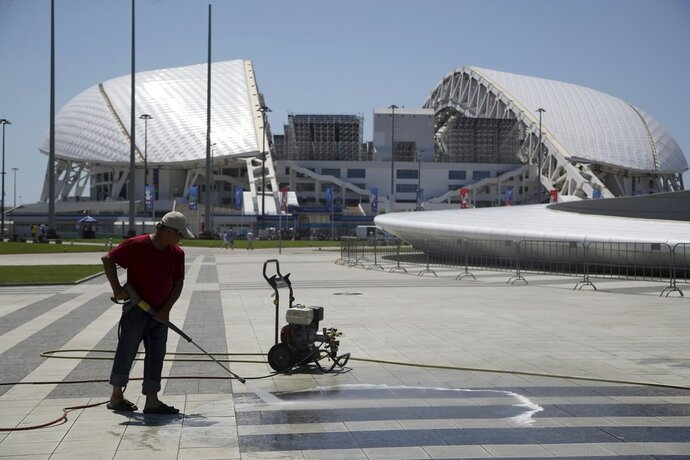 A worker cleans the area in front of Fisht Stadium ahead of the 2018 soccer World Cup in Sochi, Russia, on Thursday, June 14, 2018. (AP Photo/Thanassis Stavrakis)