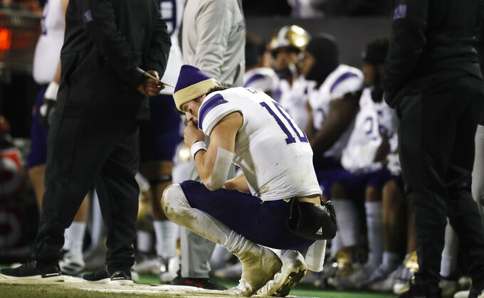 Washington quarterback Jacob Eason squats on the sideline late in the second half of the team's NCAA college football game against Colorado on Saturday, Nov. 23, 2019, in Boulder, Colo. Colorado won 20-14. (AP Photo/David Zalubowski)