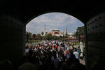 FILE - In this Friday, Aug. 17, 2018 file photo, visitors walk towards the Byzantine-era Hagia Sophia, one of Istanbul's main tourist attractions, in the historic Sultanahmet district of Istanbul. The 6th-century building is now at the center of a heated debate between conservative groups who want it to be reconverted into a mosque and those who believe the World Heritage site should remain a museum. (AP Photo/Lefteris Pitarakis, File)